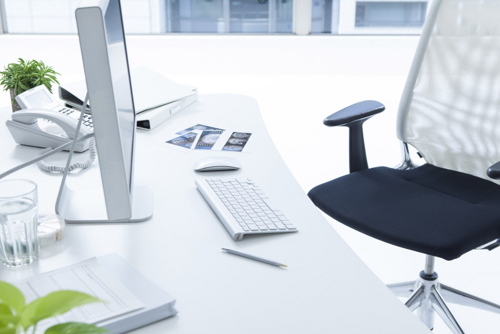 clean white commercial office desk with desktop computer phone books and chair