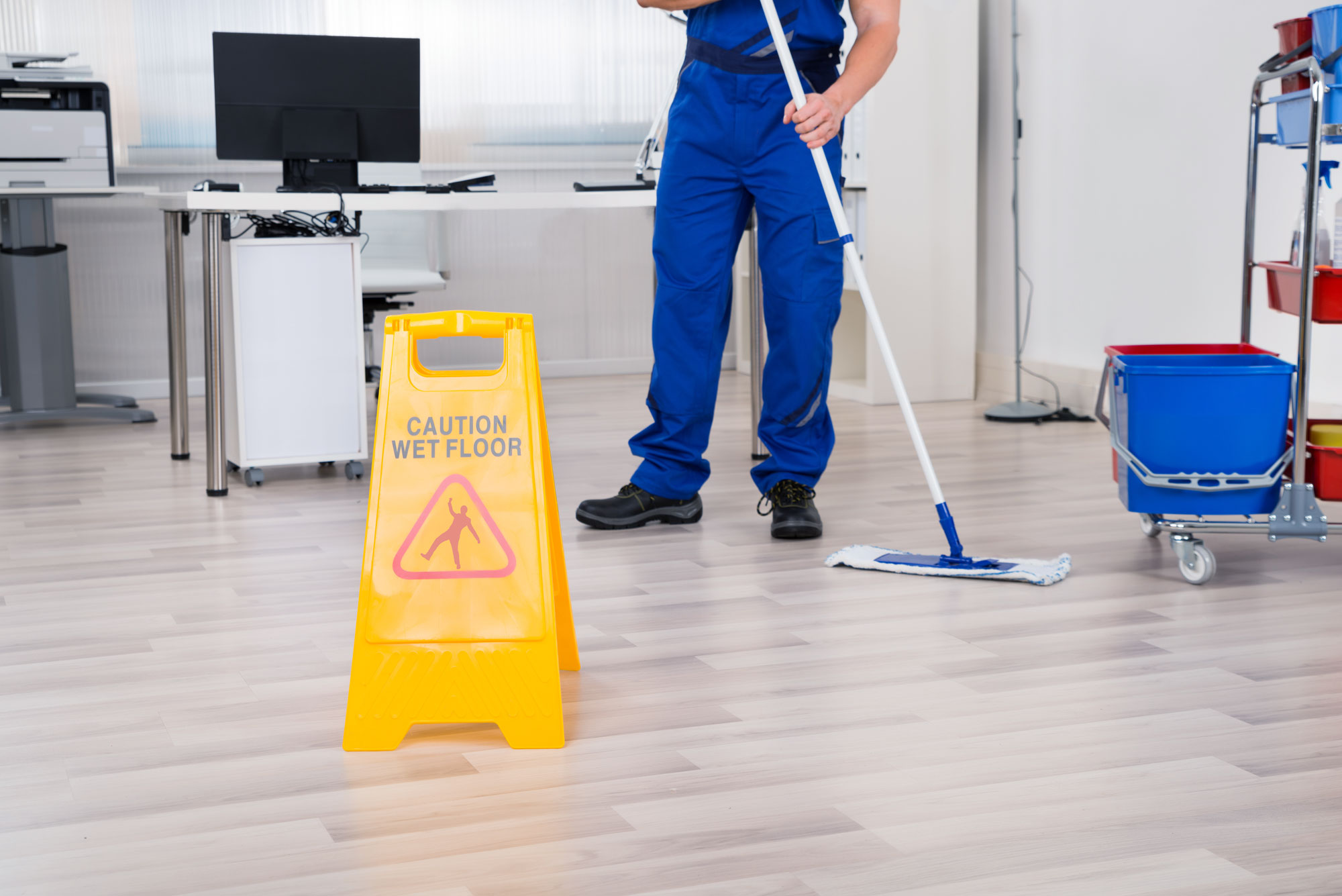 janitor wearing blue uniform mopping commercial office with wet floor sign propped up