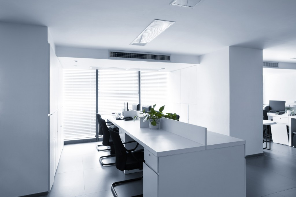 white commercial office with clean group of desks and bright light streaming in