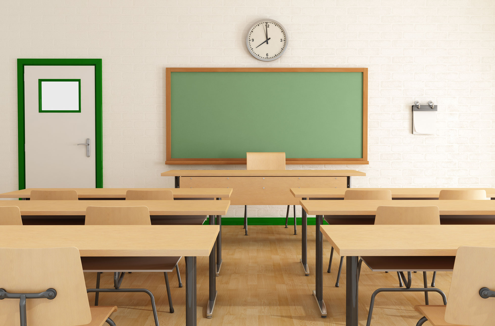 classroom with empty wooden desks and green chalkboard