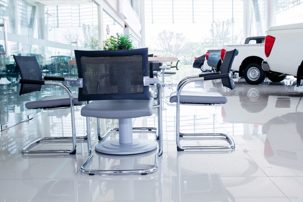 table and chairs sitting on spotless shiny floor inside of car dealership