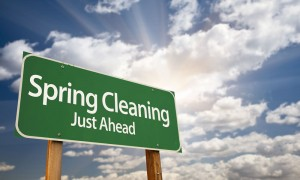road sign that reads spring cleaning just ahead with cloudy sky in the background